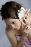 Schönes Mädchen in hörendem Shell der Badekurortbehandlungen stockfotos