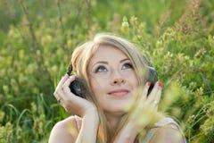 Schönes Mädchen hört Musik in der Wiese Stockbild
