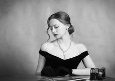 Schönes Mädchen im Abendkleid, das an einem Tisch mit Zeitschriften und einer Kamera sitzt stockfoto