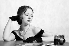 Schönes Mädchen im Abendkleid und in den langen Handschuhen, Sitzen am Tisch mit Zeitschriften und eine Kamera lizenzfreie stockfotos