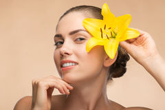 Schönes Mädchen im Badekurort mit Blume nahe ihrem Gesicht stockfoto