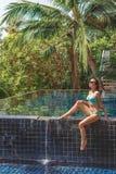 schönes Mädchen im Bikini, der auf Poolside sitzt stockfoto