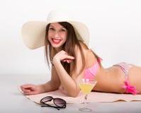 Schönes Mädchen im Bikini, in der Sonnenbrille und in einem großen Hut, der auf dem Badetuch steht neben einem Glas des Cocktails Stockfotos