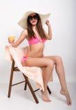 Schönes Mädchen im Bikini, in der Sonnenbrille und in einem großen Hut, der auf einem Klappstuhl, seine Hand mit einem Glas des C stockbild