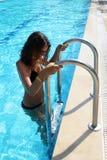 Schönes Mädchen im blauen Badeanzug und in den Sonnenbrillen betrachtet Kamera und lächelt bei der Stellung auf Leiter des Pools Lizenzfreie Stockfotografie