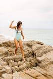 Schönes Mädchen im blauen Badeanzugweg auf großem Stein Stockfoto