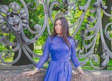 Schönes Mädchen im blauen Kleid, das am Schmiedeeisenzaun aufwirft Lizenzfreie Stockfotos