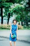 Schönes Mädchen im blauen Kleid in den Fadenkreuzen mit Geldbeutel Lizenzfreie Stockfotos