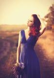Schönes Mädchen im blauen Kleid mit Blumenstrauß stockfotografie