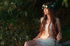 Schönes Mädchen im Blumenkranz sitzt draußen Stockfoto
