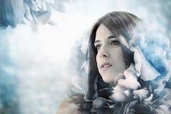 Schönes Mädchen im eleganten Blumen-Hintergrund Stockfoto