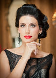 Schönes Mädchen im eleganten schwarzen Kleid, das in der Weinleseszene aufwirft Junge Schönheit, die luxuriöses Kleid trägt Verlo Lizenzfreie Stockfotos