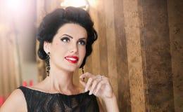 Schönes Mädchen im eleganten schwarzen Kleid, das in der Weinleseszene aufwirft Junge Schönheit, die luxuriöses Kleid trägt Verlo Stockbilder