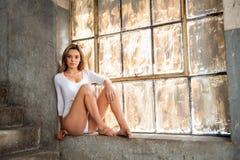 Schönes Mädchen im Fenster eines verlassenen Gebäudes Stockfotos