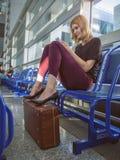 Schönes Mädchen im Flughafenabfertigungsgebäude mit einem Telefon in seiner Hand Lizenzfreie Stockbilder