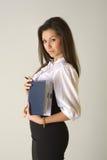 Schönes Mädchen im Geschäftsausstattungs-Holdingnotizbuch Stockfotos