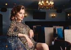 Schönes Mädchen im goldenen Kleid, das an der Stange im restaur sitzt Lizenzfreies Stockbild
