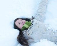 Schönes Mädchen im grünen Lügen im Schnee Stockfotografie