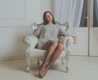 Schönes Mädchen im Hemd, das in einem Weinlesestuhl sitzt Stockbild