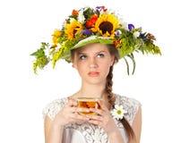 Schönes Mädchen im Hut der Blumen und der Tasse Tee Stockfotos