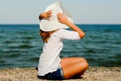Schönes Mädchen im Hut, der draußen durch das Meer sitzt Lizenzfreies Stockbild