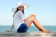 Schönes Mädchen im Hut, der draußen durch das Meer stillsteht Lizenzfreie Stockfotografie