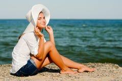 Schönes Mädchen im Hut draußen durch das Meer u. den Himmel Stockbilder