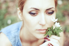 Schönes Mädchen im Hut mit weißen Frühlingsblumen Lizenzfreie Stockfotografie