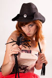Schönes Mädchen im Hut und in der Peitsche Stockbild