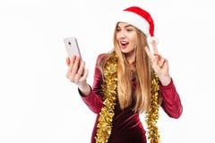 Schönes Mädchen im Hut von Santa Claus und von Kleid, mit einem intelligenten stockfoto