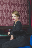 Schönes Mädchen im Kasino, das am Kasinotisch sitzt Stockfoto