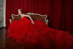 Schönes Mädchen im langen roten Kleid und in der königlichen Krone Lizenzfreie Stockfotos