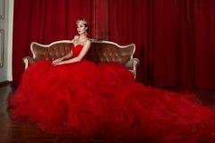 Schönes Mädchen im langen roten Kleid und in der königlichen Krone Stockbilder
