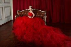 Schönes Mädchen im langen roten Kleid und in der königlichen Krone Stockfotos