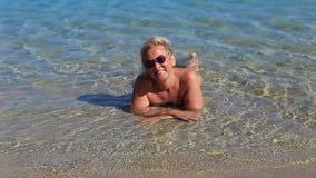 Schönes Mädchen im Meer auf dem Sand stock video