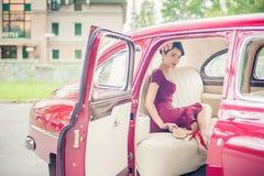 Schönes Mädchen im purpurroten Kleid, das innere Kirschretro- Auto aufwirft Stockbild