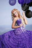 Schönes Mädchen im purpurroten Kleid mit Ballonen Stockfotografie