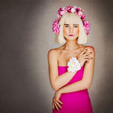 Schönes Mädchen im rosa Kleid mit Blumenhauptzusatz Stockfotos