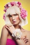 Schönes Mädchen im rosa Kleid mit Blumenhauptzusatz Stockfotografie