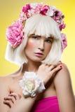 Schönes Mädchen im rosa Kleid mit Blumenhauptzusatz Stockbild
