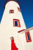 Schönes Mädchen im Rot mit einem Leuchtturm Lizenzfreies Stockfoto