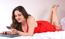 Schönes Mädchen im roten Kleid zu Hause kaufend lizenzfreies stockfoto