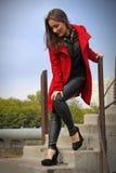 Schönes Mädchen im roten Mantel, der auf der Treppe in einem würdevollen steht lizenzfreie stockbilder