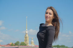 Schönes Mädchen im Schwarzen auf dem Hintergrund der Kirche Lizenzfreies Stockfoto