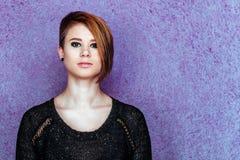 Schönes Mädchen im schwarzen Hemd auf einem purpurroten Hintergrund Stockfotos