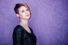 Schönes Mädchen im schwarzen Hemd auf einem purpurroten Hintergrund sideway Stockfoto