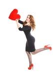 Schönes Mädchen im schwarzen Kleid mit Rot hören auf einem weißen Hintergrund Lizenzfreie Stockfotos