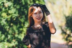 Schönes Mädchen im schwarzen Weinlesekleider- und -handhandschuh Frau im Retro- Kleid Retro- Art und Weise Rote Lippen Stockfotografie