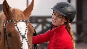 Schönes Mädchen im Sturzhelm, der draußen ein Pferd streicht stock video footage