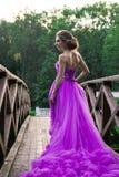 Schönes Mädchen im violetten Kleid unter im Garten Stockbilder